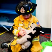 boy dressed as firefighter playing in pet vet.