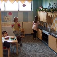 Girls playing in pretend kitchen