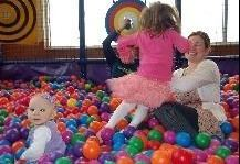 Kids jumping on parents in ball pit
