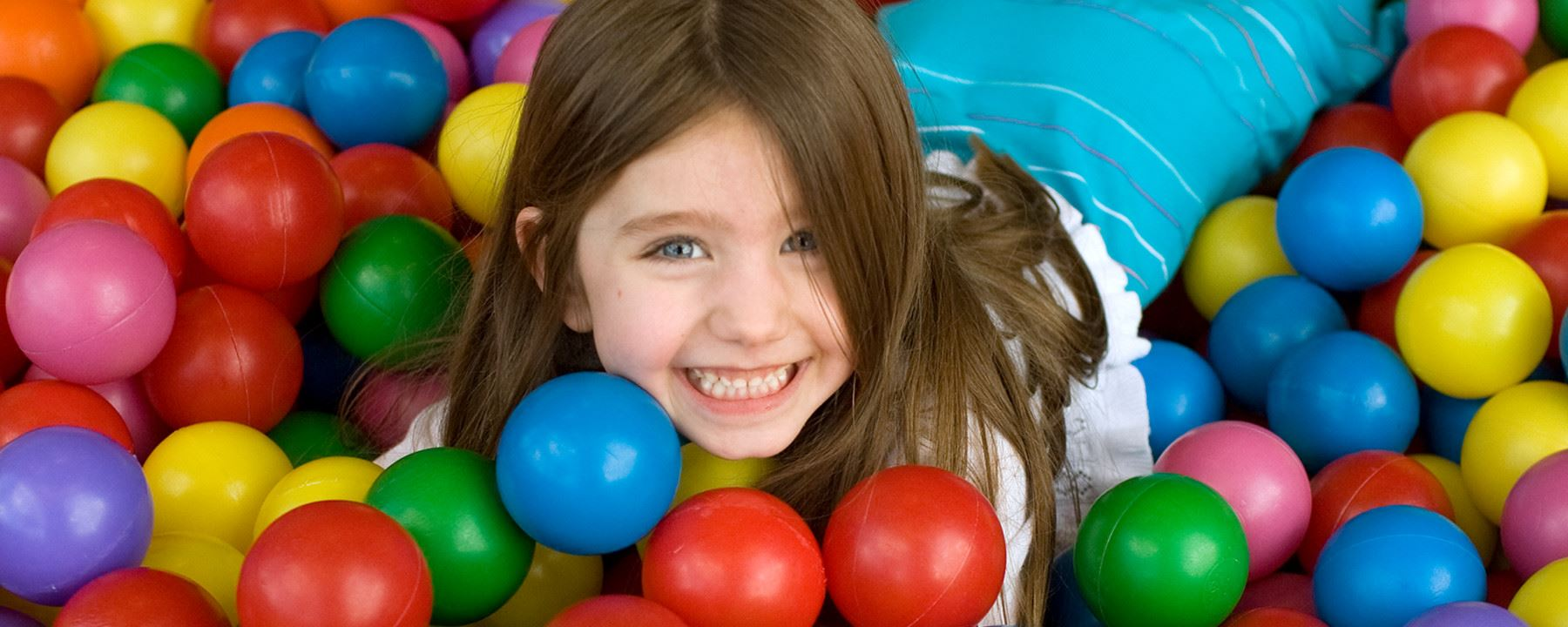 Little girl playing in ball pit